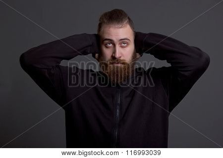 Young Man With A Beard Covers His Ears