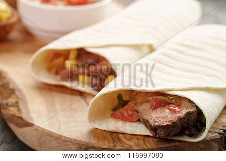 closeup photo of fresh homemade burritos with beef on wood board