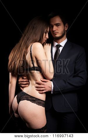 Men In Suite And Woman In Underwear Next To Each Other