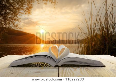 Open book at wooden table on natural blurred background. Heart books page. Back to school. Copy Spac