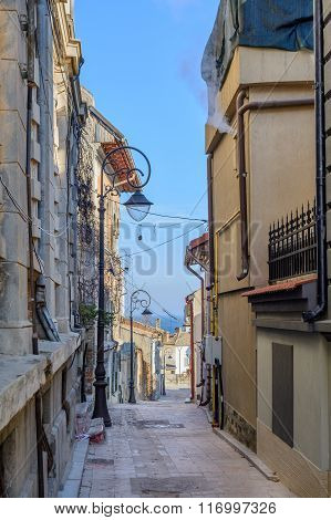 Narrow Street Between Buildings In City. Picture Of Narrow Isolated Street Between Several City Buil