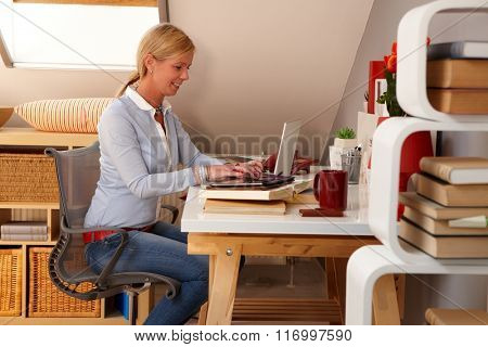 Happy young woman working at home, sitting at desk, using laptop computer.