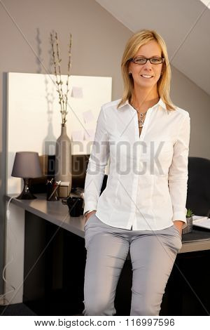 Blonde businesswoman smiling in office, hands in pockets, looking at camera.