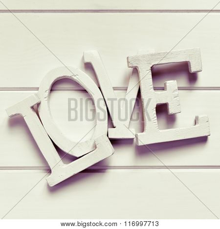white three-dimensional letters forming the word love, on a white background, with a filter effect