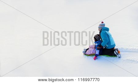 Kids sledding down snowy hill on sled fast speed