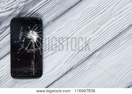 Modern broken mobile phone and money on white wooden background. Copy space. Top view