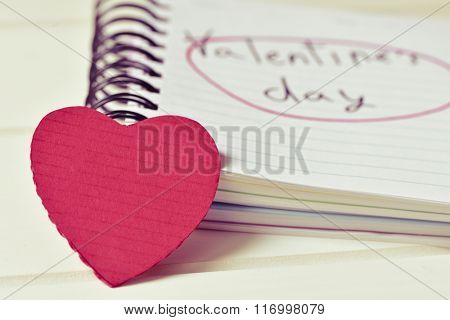 closeup of a red hart and a notebook with the text valentines day handwritten in it, on a white surface, with a filter effect