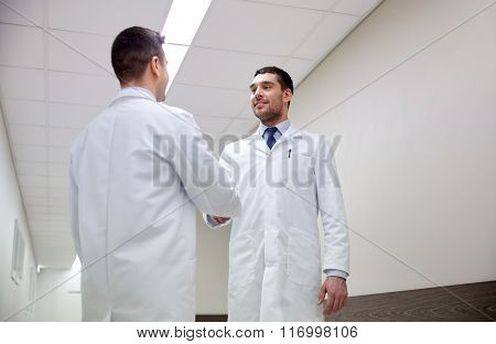 smiling doctors at hospital doing handshake