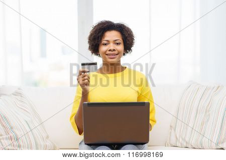 happy african woman with laptop and credit card