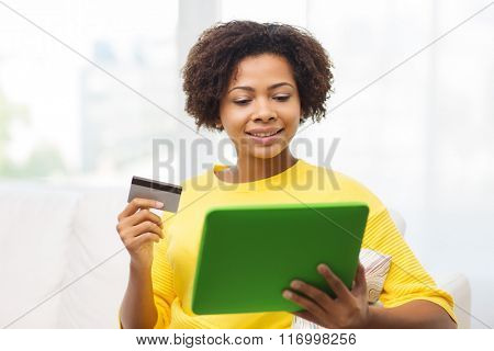 happy african woman with tablet pc and credit card