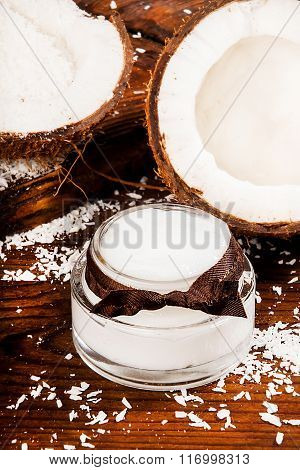Coconut and homemade coconut cream on a wooden background