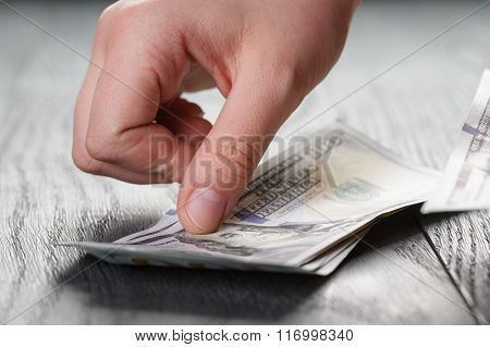young female hands count dollar bills on wood table