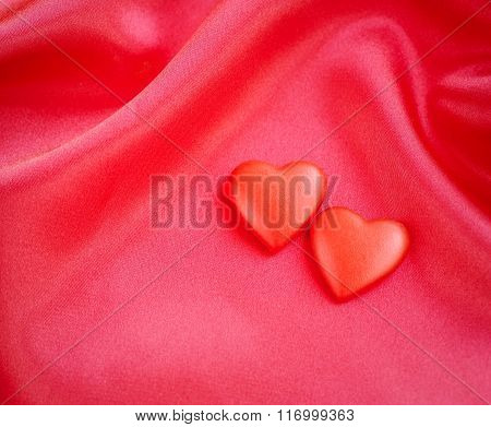 Two Red Hearts On Satin Fabric Background
