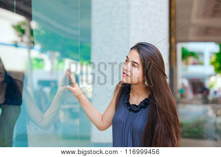 Biracial Teen Girl  Window Shopping In Urban Setting Downtown