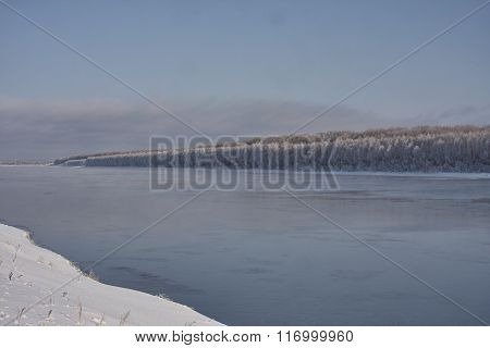Irtish in deep autumn snow on banks hoarfrost forest clear blue sky. Russia.