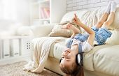 little girl with headphones at home. child girl listening to music.  poster