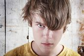 stock photo of delinquency  - A troubled teen peers through his hair - JPG
