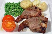 stock photo of lamb chops  - grilled lamb chop with rosemary potatoes tomatoes peas - JPG
