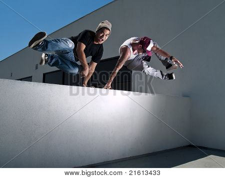 2 men doing a parkour jump over the wall