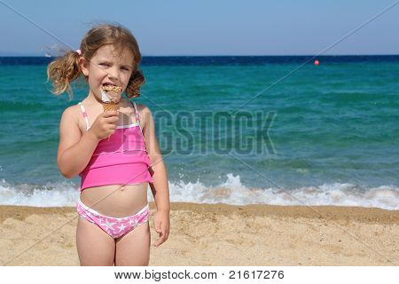 little girl eat ice cream on the beach