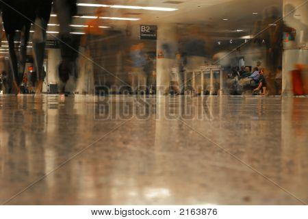 Passengers Walking Down The Concourse Towards Their Planes.