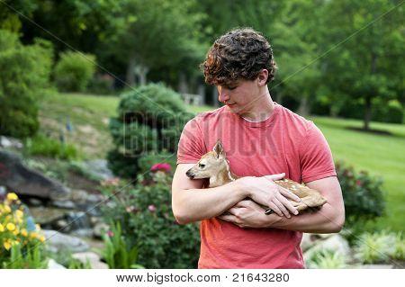 Boy Holding Newborn Fawn