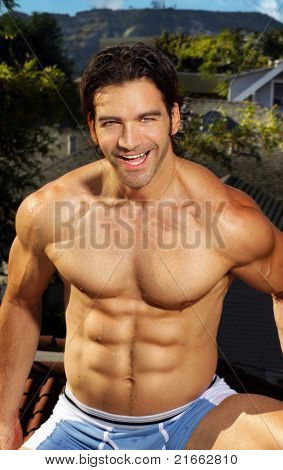 Outdoor portrait of a hunky male fitness model having a good time laughing and smiling