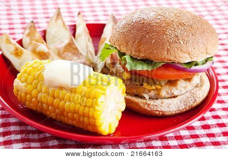 Healthy turkey burger on a whole grain bun, with baked potato wedges and corn on the cob, served on a red and white checkered tablecloth.