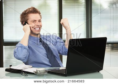 Happy businessman hearing good news on phone