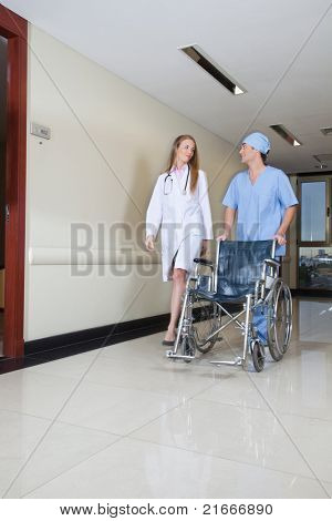 Doctor walking with male nurse pushing wheelchair