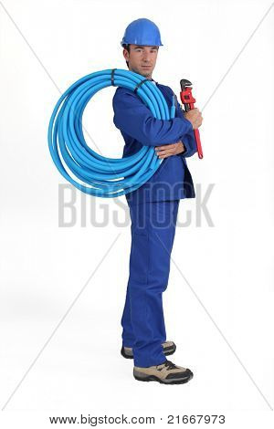 Man holding blue tube, wrench and hardhat