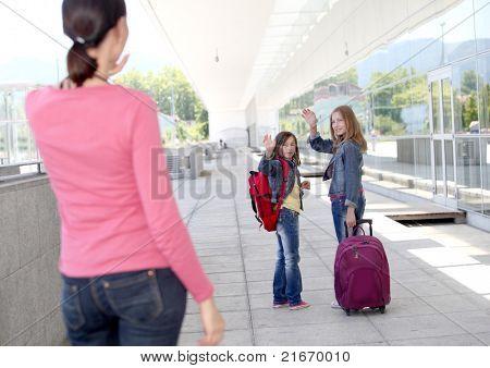 School girls waving goodbye at their mother