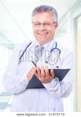 Closeup portrait of a happy young doctor with stethoscope in hospital writing a receipt