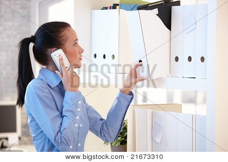 Office worker woman talking on mobile phone while choosing file folder from shelf.?