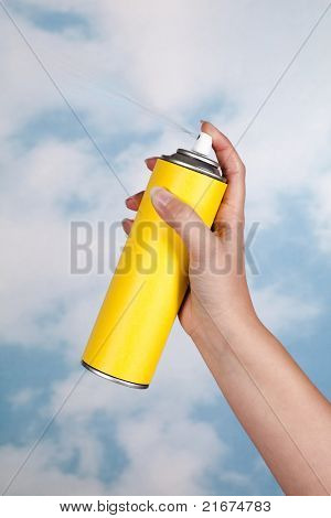 Hand spraying a substance like insecticide into open air