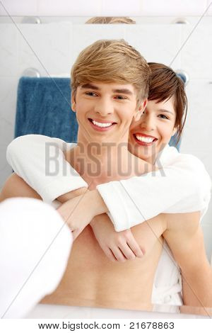 Young happy couple at bathroom. Isolated on white.
