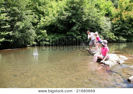 Family playing ricochet in river