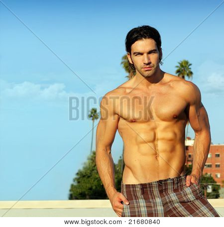 Portrait of a hunky shirtless male model outdoors