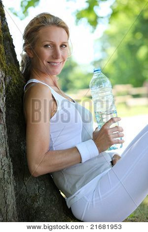 Sporty woman taking a break from a country run to have a drink