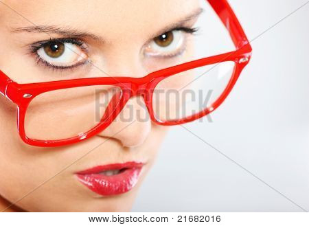 A close-up of a young woman in red glasses over light background