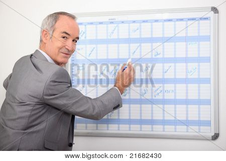 Older businessman writing on a wall planner