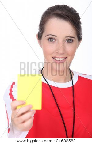 Female referee holding yellow card
