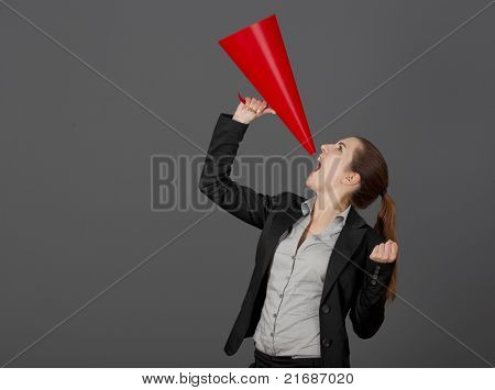 Business young woman speaking to a megaphone, over a grey background