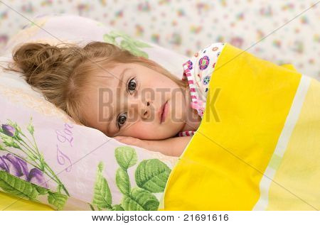 The little girl in bed.