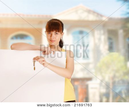 A woman is holding a key and is standing outside with white blank