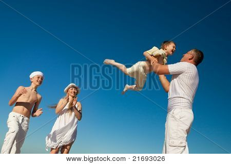 Boy flying on his father's hands at beach