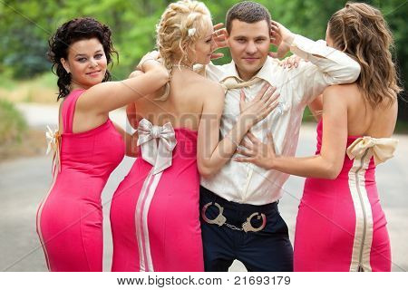 Bridesmaids standing with Groom in manacles