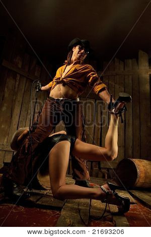 Strict cowboy with black Leather Flogging Whip in his hand clutching bondwoman between his legs