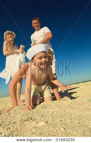 Família alegre, se divertindo na praia nas férias