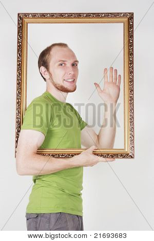 Man In Green Shirt Holding Decorative Picture Frame And Smiling